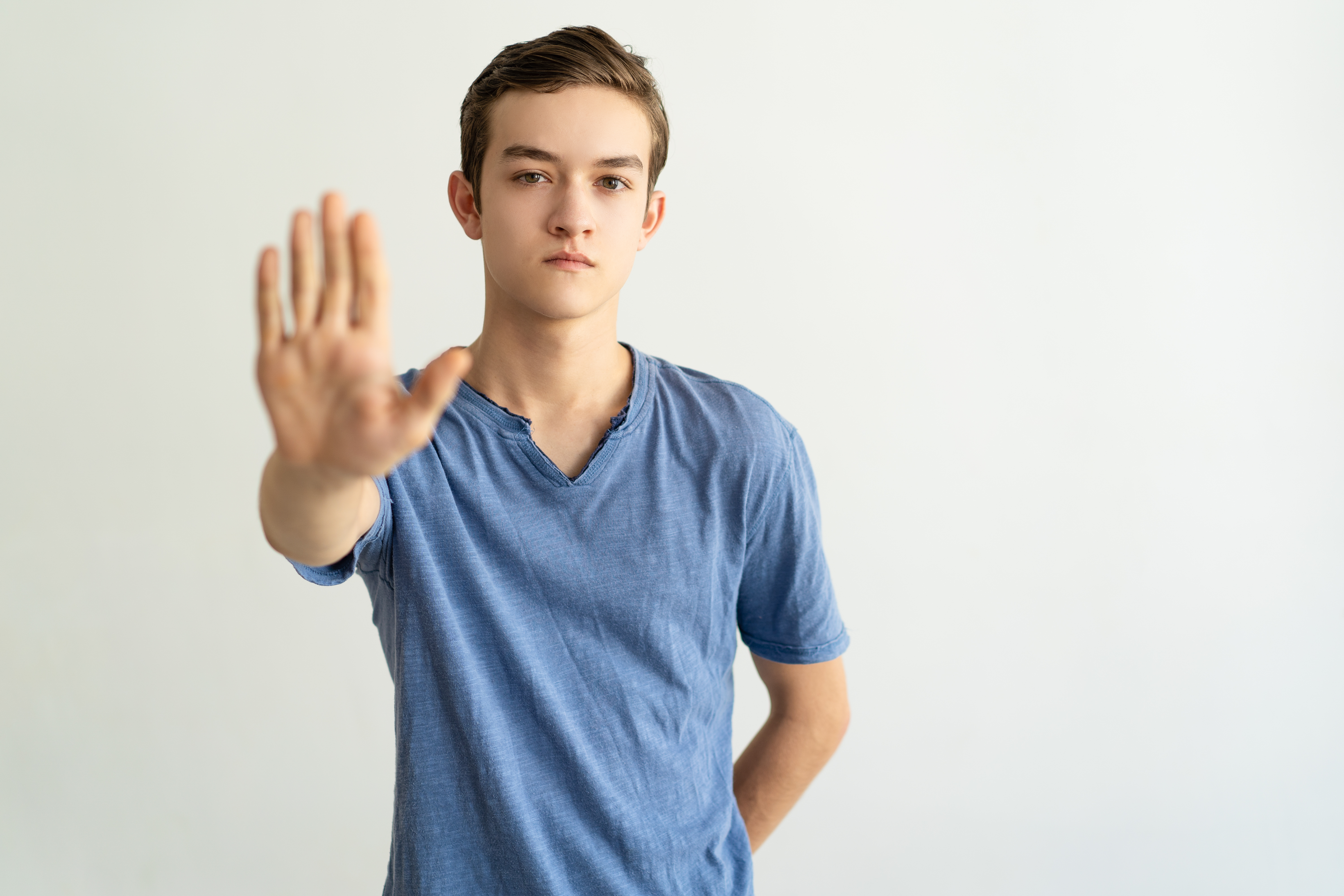 Serious strict young man making restriction gesture